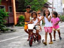 Молодые азиатские дети играя и ехать велосипед Стоковые Изображения