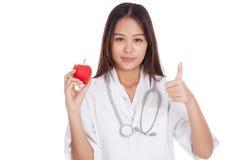 Молодые азиатские женские большие пальцы руки доктора вверх с яблоком Стоковая Фотография RF