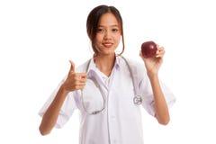Молодые азиатские женские большие пальцы руки доктора вверх с яблоком Стоковая Фотография