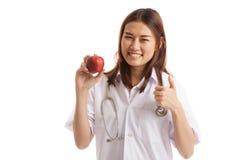 Молодые азиатские женские большие пальцы руки доктора вверх с яблоком Стоковые Фотографии RF