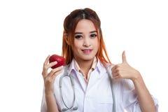 Молодые азиатские женские большие пальцы руки доктора вверх с яблоком Стоковое фото RF