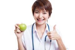 Молодые азиатские женские большие пальцы руки доктора вверх с яблоком Стоковые Изображения