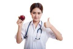 Молодые азиатские женские большие пальцы руки доктора вверх с яблоком Стоковое Изображение RF