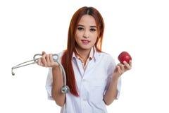 Молодые азиатские женские яблоко и стетоскоп владением доктора Стоковые Изображения
