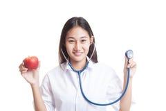 Молодые азиатские женские яблоко и стетоскоп владением доктора Стоковые Изображения RF