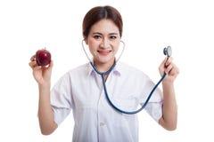 Молодые азиатские женские яблоко и стетоскоп владением доктора Стоковое фото RF