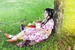 Молодые азиатские женщины нося солнечные очки усмехаясь счастливо и слушают Стоковое фото RF