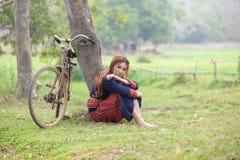 Молодые азиатские женщины сидя рядом с деревом с велосипедом в поле a риса Стоковое Изображение RF