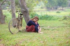 Молодые азиатские женщины сидя рядом с деревом с велосипедом в поле a риса Стоковые Изображения