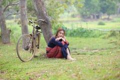 Молодые азиатские женщины сидя рядом с деревом с велосипедом в поле a риса Стоковые Фотографии RF