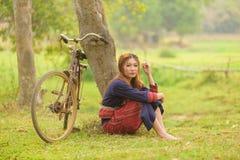 Молодые азиатские женщины сидя рядом с деревом с велосипедом в поле a риса Стоковое Изображение