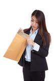 Молодые азиатские конверты коричневого цвета внутренности взгляда сюрприза коммерсантки Стоковая Фотография RF