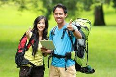 Молодые азиатские пары стоя на парке держа ПК таблетки показывают Стоковое Фото