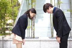 Молодые азиатские руководители бизнеса обхватывая друг к другу стоковая фотография rf