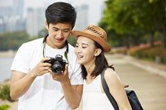 Молодые азиатские туристы проверяя изображения в камере Стоковые Изображения