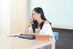 Молодые азиатские worling и тревога женщины на столе в офисе Стоковое Изображение RF