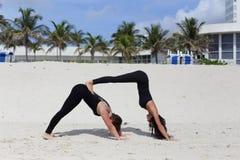 Молодые дамы выполняя йогу на песке Стоковые Изображения