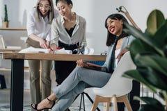 Молодые архитекторы в официально носке работая с светокопией и цифровой таблеткой в офисе Стоковые Фото
