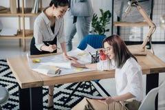 Молодые архитекторы работая с светокопиями и цифровой таблеткой в современном офисе Стоковое Изображение RF