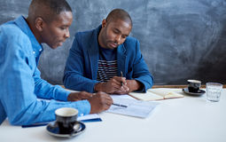 Молодые африканские бизнесмены работая совместно в современном офисе Стоковые Изображения