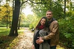 Молодые беременные пары в осени снаружи стоковая фотография rf