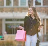 Молодые белокурые женские покупки при розовые и красные сумки держа сотовый телефон Стоковая Фотография RF