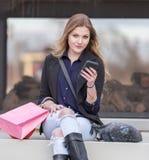 Молодые белокурые женские покупки при розовые и красные сумки держа сотовый телефон Стоковое Изображение