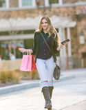 Молодые белокурые женские покупки при розовые и красные сумки держа сотовый телефон Стоковая Фотография
