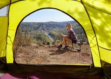 Молодые белокурые туристы женщины в лагере на скале над рекой и передней частью Стоковое Изображение