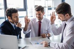 Молодые бизнесмены в официально носке обсуждая диаграммы дела и показывая одобренный знак Стоковое фото RF
