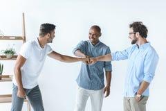 Молодые бизнесмены держа руки совместно Стоковые Изображения