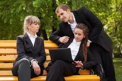 Молодые бизнесмены используя компьтер-книжку в парке города Стоковая Фотография