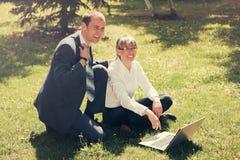 Молодые бизнесмены используя компьтер-книжку в парке города Стоковое фото RF