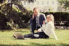 Молодые бизнесмены используя компьтер-книжку в парке города Стоковые Изображения