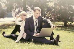 Молодые бизнесмены используя компьтер-книжку в парке города Стоковые Фотографии RF