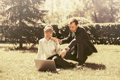 Молодые бизнесмены используя компьтер-книжку в парке города Стоковые Фото