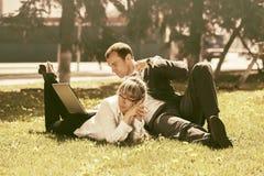 Молодые бизнесмены используя компьтер-книжку в парке города Стоковое Фото