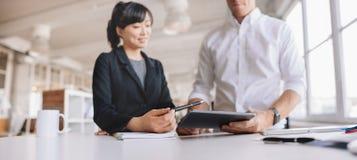 Молодые бизнесмены используя цифровую таблетку на работе Стоковые Фото