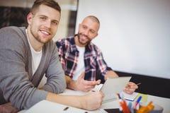 Молодые бизнесмены используя цифровую таблетку на столе в офисе Стоковые Фотографии RF