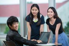Молодые бизнесмены команды сидя на столе Стоковое фото RF