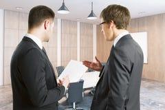 Молодые бизнесмены обсуждая контракт Стоковая Фотография