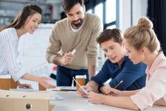 Молодые бизнесмены обсуждая новый бизнес-план на встрече Стоковое фото RF
