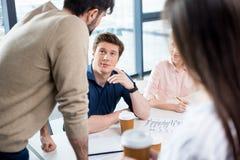 Молодые бизнесмены обсуждая новый проект на малой встрече офиса Стоковые Фото