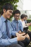 Молодые бизнесмены проверяя их сотовые телефоны Стоковые Фотографии RF