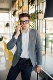 Молодые бизнесмены работая в его офисе и говоря на его мобильном телефоне Стоковая Фотография