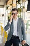 Молодые бизнесмены работая в его офисе и говоря на его мобильном телефоне Стоковые Изображения