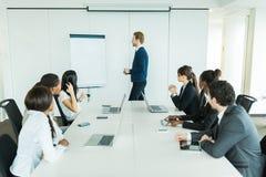 Молодые бизнесмены сидя на столе переговоров и уча Стоковая Фотография