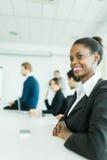 Молодые бизнесмены сидя на столе переговоров и уча Стоковая Фотография RF