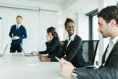 Молодые бизнесмены сидя на столе переговоров и уча Стоковое Изображение RF