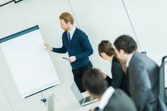 Молодые бизнесмены сидя на столе переговоров и уча Стоковые Фото
